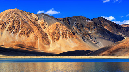 refelction: Refelction of Mountains on Pangong tso (Lake) with blue sky in background. It is huge lake in Ladakh, It is 134 km long and extends from India to Tibet. Leh, Ladakh, Jammu and Kashmir, India Editorial