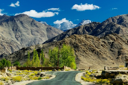 onwards: A concrete road towards beautiful rocky mountains and blue sky with peaks of Himalaya Leh Ladakh Jammu and Kashmir India Stock Photo