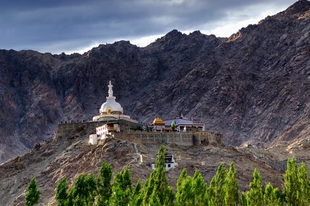 shanti: Shanti Stupa with view of dark Himalayan mountain in shade and blue sky in background,Ladakh,Jammu and Kashmir, India