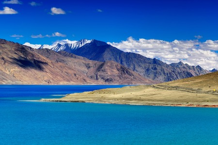 Mountains and Pangong tso Lake. It is huge lake in Ladakh, altitude 4,350 m 14,270 ft. It is 134 km 83 mi long and extends from India to Tibet. Leh, Ladakh, Jammu and Kashmir, India