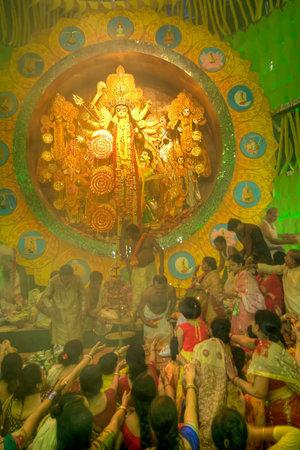 documentary: KOLKATA , INDIA - OCTOBER 1, 2014 : Priest distributing flowers for praying to Goddess Durga, Biggest religious festival of Hinduism and Kolkatas Bengali Community. Documentary editorial.