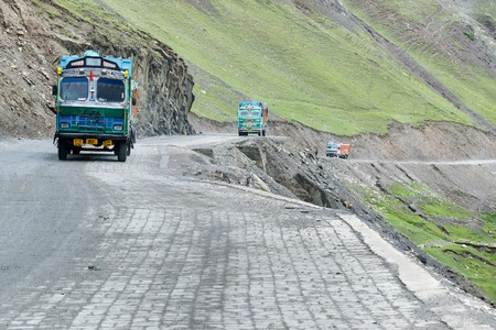 LEH, INDIA - SEPTEMBER 1, 2014 : Trucks carrying goods are passing through Zojila Pass, a high mountain pass between Srinagar and Leh at 11575 ft, 9 Km stretch. Indian National Highway.