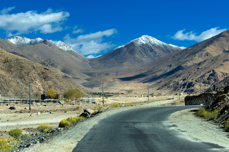 onwards: A concrete road towards beautiful rocky mountains and blue sky with peaks of Himalaya, Leh, Ladakh, Jammu and Kashmir, India
