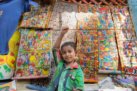 handicrafts: PINGLA, WEST BENGAL , INDIA - NOVEMBER 16TH 2015 : Unidentified playful rural child selling colourful handicrafts in Pingla village. Handicrafts are rural Industry in West Bengal.