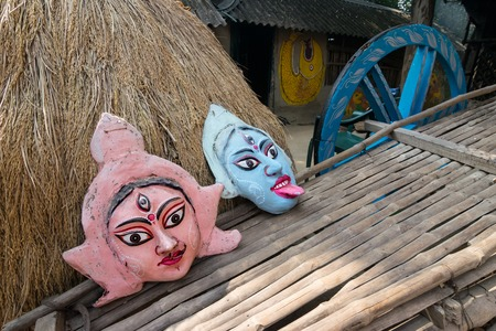 hindu god shiva: PINGLA, WEST BENGAL , INDIA - NOVEMBER 16TH 2014 : Colourful handicrafts , claymade faces of Indian Hindu God Shiva and Goddess Durga, are being prepared for sale in Pingla village, India. Editorial