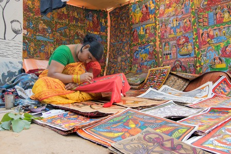 PINGLA, WEST BENGAL , INDIA - NOVEMBER 16TH 2015 : Colourful handicrafts are being prepared for sale in Pingla village by Indian rural woman worker. Handicrafts are rural Industry in West Bengal.