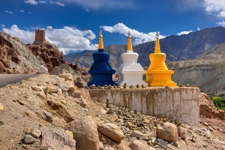 religious: Three colourful buddhist religious stupas at Leh, Ladakh, Jammu and Kashmir, India. Religious symbols in landscape,  with himalayan mountain, road and blue sky.
