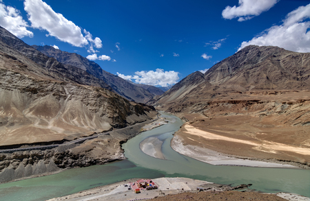 confluence: Scenic view of Confluence of Zanskar river from left and Indus rivers from up right - Leh, Ladakh, Jammu and Kashmir, India. Famous tourist spot of Ladakh for all seasons. landscape. Stock Photo