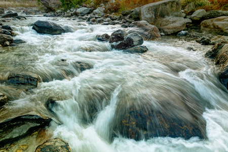 liquid state: Beautiful Reshi River water flowing through stones and rocks at dawn,  Sikkim, India. Reshi is one of the most famous rivers of Sikkim flowing through the state and serving water to many local people. Stock Photo