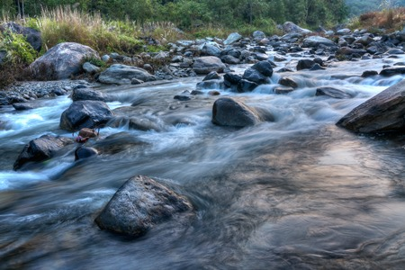 Beautiful Reshi River water flowing through stones and rocks at dawn,  Sikkim, India. Reshi is one of the most famous rivers of Sikkim flowing through the state and serving water to many local people. Stock Photo