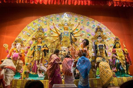 worshipping: KOLKATA , INDIA - OCTOBER 18, 2015 : Married Bengali women worshipping Durga idol at Puja pandal, shot at colored light, at Kolkata, West Bengal, India. Durga Puja is biggest religious festival of Hinduism. Editorial