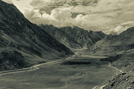 cloudy moody: Aerial view of moody and rocky landscape of Kargil, with mountain peaks and cloudy sky  in background , green valley , Leh, Ladakh, Jammu and Kashmir, India