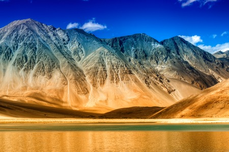 Beautiful Mountains and Pangong tso (Lake). It is a huge lake in Ladakh, extends from India to Tibet. Leh, Ladakh, Jammu and Kashmir, India. Himalayan mountains in background. Colourful stock image.