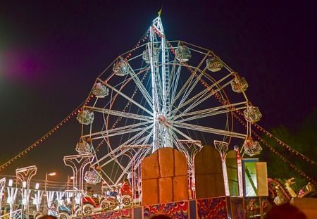 howrah: HOWRAH, WEST BENGAL , INDIA - MARCH 1ST MARCH 2015 : Roller coster ride at Howrah, West Bengal, India. Shot at night with colored lights. Stock Photo