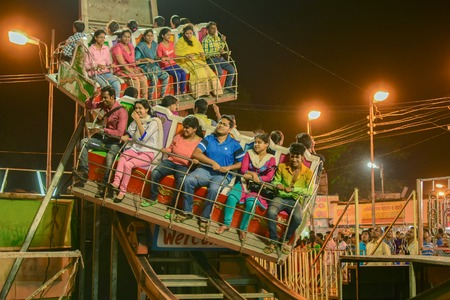 howrah: HOWRAH, WEST BENGAL , INDIA - MARCH 1ST MARCH 2015 : Young people enjoying Roller coster ride at Howrah, West Bengal, India. Shot at night with colored lights.