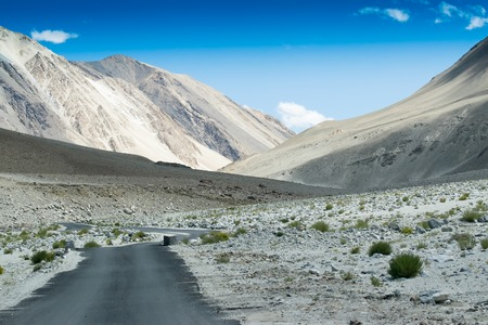 A concrete road towards beautiful rocky mountains and blue sky with peaks of Himalaya, Leh, Ladakh, Jammu and Kashmir, India
