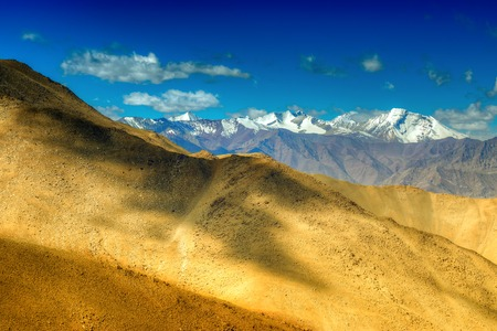 Rocky landscape of Ladakh with blue sky and ice peaks , brown stones and rocks at Changla pass, play of light and shodow on the mountain, Leh, Ladakh, Jammu and Kashmir, India