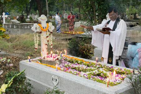 KOLKATA, WEST BENGAL , INDIA - NOVEMBER 2ND 2014 : Priest and relatives at All souls day remembrance at old cemetary at south Park Street, Kolkata. Editorial