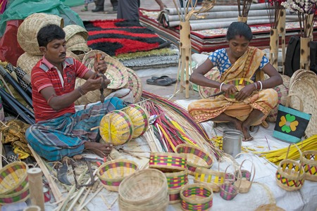 weaved: Kolkata, West Bengal, India - 28th November, 2015 : Couple weaving cane baskets, handicrafts on display during the Handicraft Fair in Kolkata. Biggest handicrafts fair in Asia.