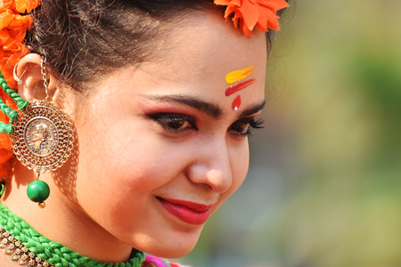 make known: KOLKATA , INDIA - MARCH 12, 2017: Beautiful young girl with spring festive make up with flowers , joyful expression at HoliSpring festival,known as Dol (in Bengali) or Holi (in Hindi) celebrating arrival of Spring.