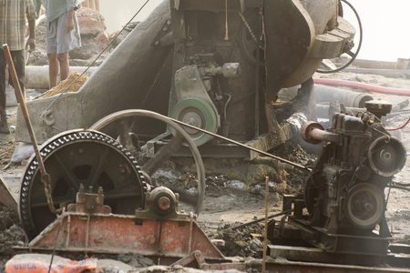 kw: KOLKATA , INDIA - APRIL 21, 2017: Indian workers working at smoke covered project site. Black smokes coming out of diesel generator polluting environment . India is developing its infrastructure. Editorial