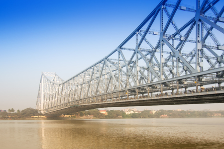 Famous Howrah Bridge connecting Howrah and Kolkata, a propped cantilever bridge with a suspended span over the Hooghly River in West Bengal, India. Commissioned in 1943. A busy transportation symbol of Kolkata.