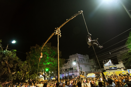 KOLKATA, WEST BENGAL, INDIA - 15 APRIL 2017: Two Hindu devotees are hanging in air from ropes and circling around, at night. Religious sports for festival called