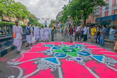 deities: KOLKATA, WEST BENGAL , INDIA - JUNE 25TH 2017 : Devotee dressed in traditional dress posing on coloured road on Rath Yatra festival. God Jagannath, Balaram and Goddess Suvadra are taken for a chariot ride.