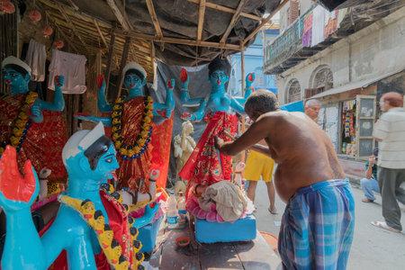KUMARTULI, KOLKATA, INDIA - OCTOBER 10, 2014 - Artist preparing clay idol to be worshipped as Goddess Kali, during Kali Puja, Hindu festival of Deepavali or Diwali. Celebtated all over India. Editorial
