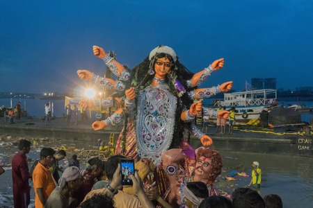 devotee: KOLKATA, WEST BENGAL, INDIA - 30 SEPTEMBER 2017: Idol of Goddess Durga is being immersed in Holy river Ganges. Celebrated by Hindus as