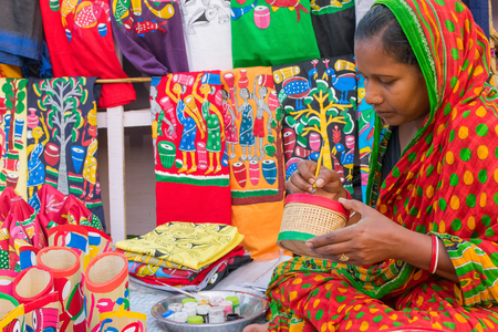 KOLKATA, WEST BENGAL , INDIA - DECEMBER 3RD 2016 : Colourful handicrafts are being prepared by middle aged woman for sale in Kolkata in handicrafts trade fair. It is rural Industry in West Bengal.