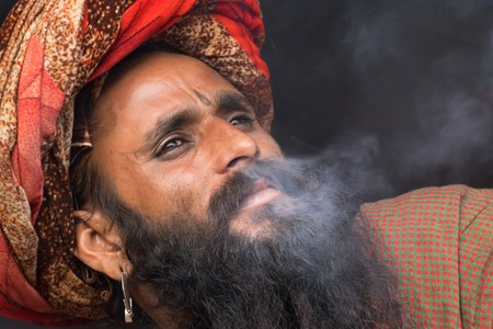 BABUGHAT, KOLKATA, WEST BENGAL  INDIA - 11TH JANUARY 2015 : Indian Hindu Sadhu smoking marijuana, locally called Ganja, a form of canabis sativa . On his way to Gangasagar, India.