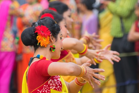 KOLKATA , INDIA - MARCH 12, 2017: Dancing poses of girl dancers , dressed in yellow and red coloured sari (traditional Indian dress) dancing at Spring festival, ie, Dol / Holi. Stock Photo - 96136313
