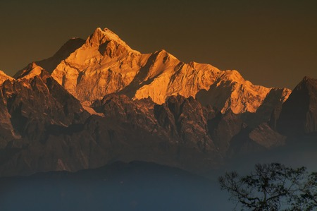 Beautiful first light from sunrise on Mount Kanchenjungha, Himalayan mountain range, Sikkim, India. Orange tint on the mountains at dawn. Stock fotó - 99350052