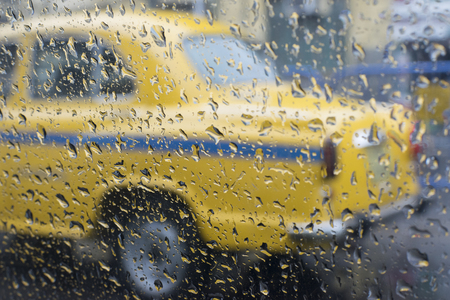 Raindrops falling on glass, abstract blurs - monsoon stock image of traditional yellow taxi of Kolkata (formerly Calcutta) city , West Bengal, India