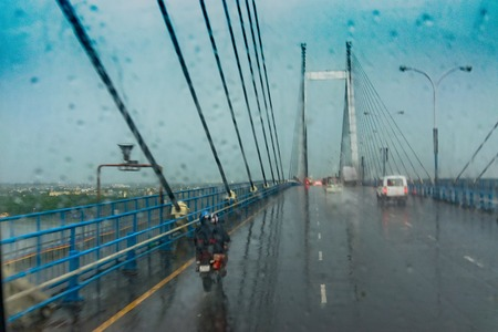 Vidyasagar Setu (Bridge) over river Ganges, known as 2nd Hooghly Bridge in Kolkata,West Bengal, India. Abstract image shot aginst glass with raindrops all over it, monsoon image of Kolkata.