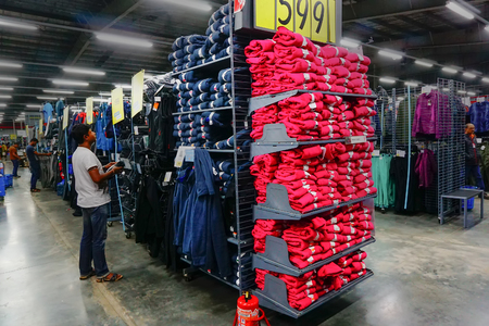 ULUBERIA, HOWRAH, WEST BENGAL  INDIA - 18TH MARCH 2018 : Indian man checking out Sports clothes inside at Dechathlon S.A. - worlds largest sporting goods retailer. Clerance sale.
