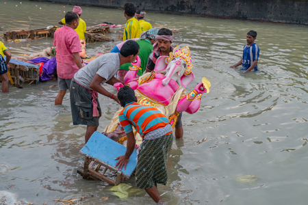 KOLKATA, WEST BENGAL, INDIA - 30 SEPTEMBER 2017: Idol of Lord Ganesha is being immersed in Holy river Ganges. Celebrated by Hindus as