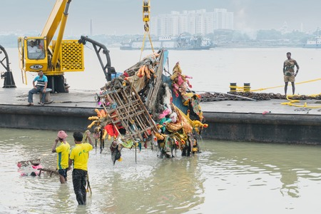 KOLKATA, WEST BENGAL, INDIA - 30 SEPTEMBER 2017: Grabage of immersed Goddess Durga idol is being lifted up from holy river Ganges by crane. Editorial