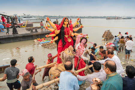 KOLKATA, WEST BENGAL, INDIA - 30 SEPTEMBER 2017: Idol of Goddess Durga is being immersed in Holy river Ganges, called