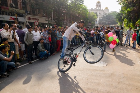 KOLKATA, WEST BENGAL, INDIA - MARCH 1ST 2015 : Cyclist boy showing off bicycle skills at Park Street for Reklamní fotografie - 112500102