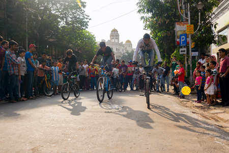 KOLKATA, WEST BENGAL, INDIA - MARCH 1ST 2015 : Three Cyclist boys showing off bicycle skills at Park Street for