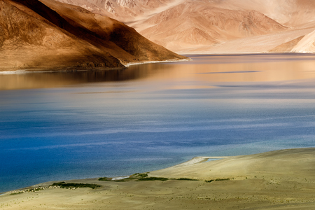Rocks and reflection of Mountains on Pangong tso (Lake) with blue sky. It is huge lake in Ladakh, It is 134 km long and extends from India to Tibet. Leh, Ladakh, Jammu and Kashmir, India Stock Photo