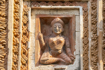 Beautiful lady in asana (a sitting posture), showing up as a phylosophical symbol, Terracotta art works on the temple walls of Lalji temple of Kalna, West Bengal, India . Art made of burnt bricks.
