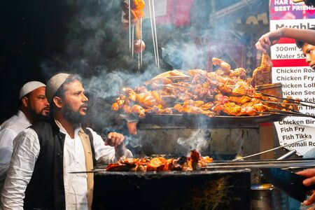 OLD MARKET, NEW DELHI, INDIA - OCTOBER 28 2018 : Spicy chicken seekh kababs are being sold to Muslim men, being stacked on the road side for sale as street food. It is famous for various street foods.