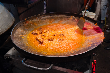 Spicy chicken curry is being prepared with heat at evening for sale as street food in Old Delhi market. The place is very famous for spicy Indian non vegetarian street foods.