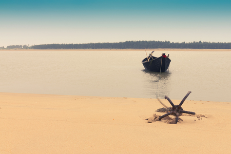 Moody image of a boat on water tied by a rope with an anchor on river bed at Tajpur, West Bengal, India. Minimalistic image. Banque d'images