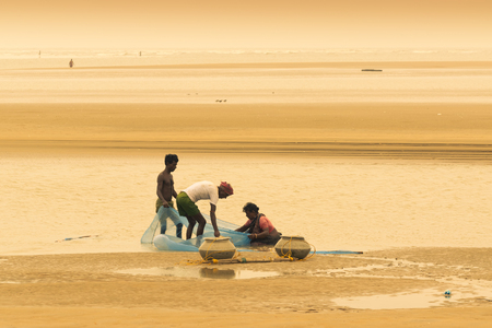 TAJPUR, WEST BENGAL, INDIA - JUNE 22ND, 2014 : A fisherman catching fish with his wife and son with fishing net at seashore of Bay of Bengal. Fishing is means of livelihood for many people at Tajpur.