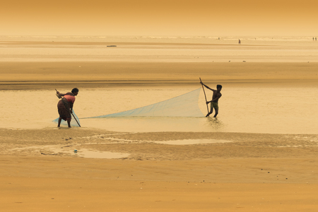 TAJPUR, WEST BENGAL, INDIA - JUNE 22ND, 2014 : A fishermans wife and son catching fish with fishing net at seashore of Bay of Bengal in the morning. Fishing is livelihood for many people at Tajpur.