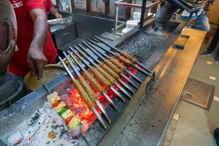 Spicy chicken seekh kababs are being grilled with heat in barbeque with metal skewers,at evening for sale as street food in Old Delhi market. It is famous for spicy Indian non vegetarian street foods. Фото со стока